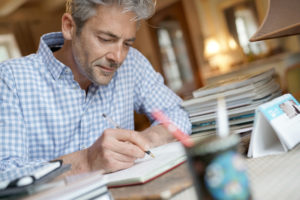 Mature man sitting at desk writing on notebook